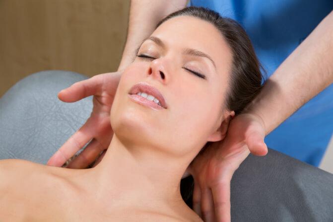 A female patient receives craniosacral fascial therapy