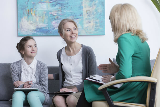 Mother and daughter talking to a craniosacral fascial therapist