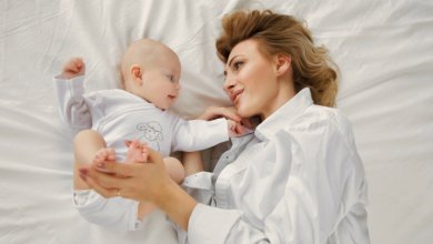 Mother and infant smile in bed - Gillespie Approach–Craniosacral Fascial Therapy